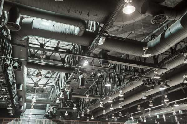 HVAC Duct Cleaning, Ventilation pipes in silver insulation material hanging from the ceiling inside new building