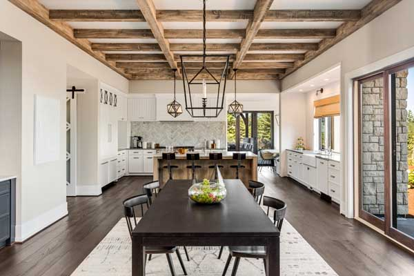 Stunning kitchen and dining room in new luxury home Wood beams and elegant pendant lights accent this beautiful open plan dining room and kitchen